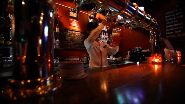 A waitress pours a pint at a bar
