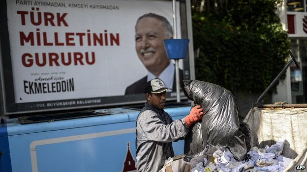 A man collects rubbish in front of a poster of Ekmeleddin Ihsanoglu
