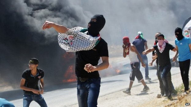 Palestinian protesters throw rocks at Israeli troops near the West Bank town of Nablus (8 August 2014)