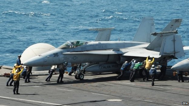 A handout picture provided by the US Navy shows sailors guiding an F/A-18C Hornet on the flight deck of the US aircraft carrier USS George H.W. Bush (CVN 77), in the Arabian Gulf, 08 August 2014