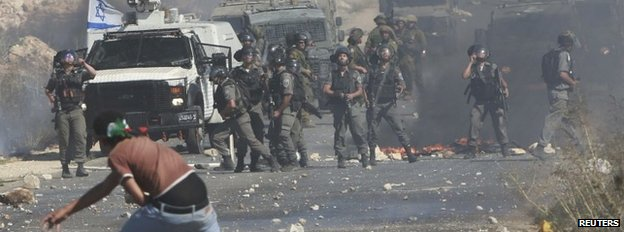 A Palestinian protester throws a stone at Israeli troops