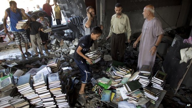 Palestinians collect stacks of books in the Martyr Imam Hassan al-banna mosque in Gaza City (9 August 2014)