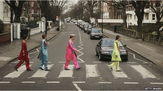 Actors play the part of the Beatles crossing a zebra crossing outside the Abbey Road studio