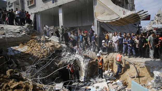 Palestinians are gathered at the site of the al-Qassam mosque hit by an Israeli strike (9 August 2014)