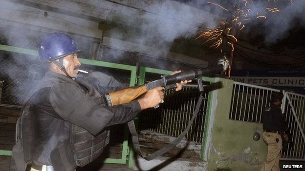 A policeman fires tear gas to disperse supporters of Tahirul Qadri in Lahore 8 August 2014