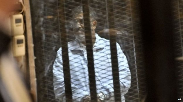 Egypt's ousted President Mohammed Morsi stands inside a glassed-in defendant's cage (28 January 2014)