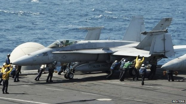Sailors guide an F/A-18C Hornet on the flight deck of the USS George H W Bush (8 August 2014)
