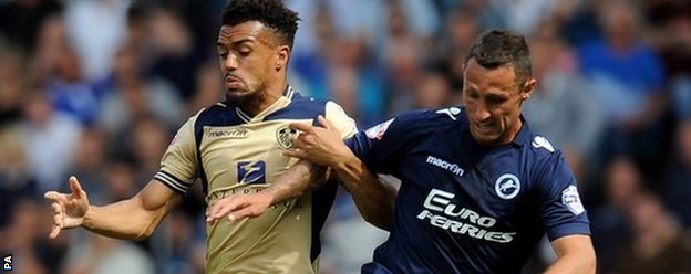 Leeds United's Nicky Ajose (left) and Millwall's Scott McDonald battle for the ball at the New Den