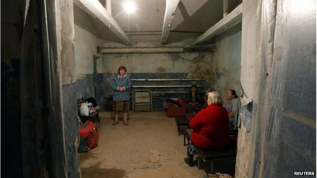 Local residents chat inside a bomb shelter where they are seeking refuge during what they say is shelling in Donetsk August 9