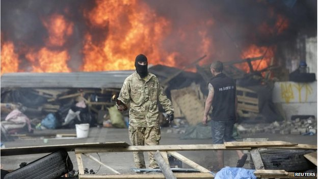 A protester holds a petrol bomb as he tries to prevent municipal workers and volunteers from clearing away barricades and tents at Independence Square in Kiev August 9