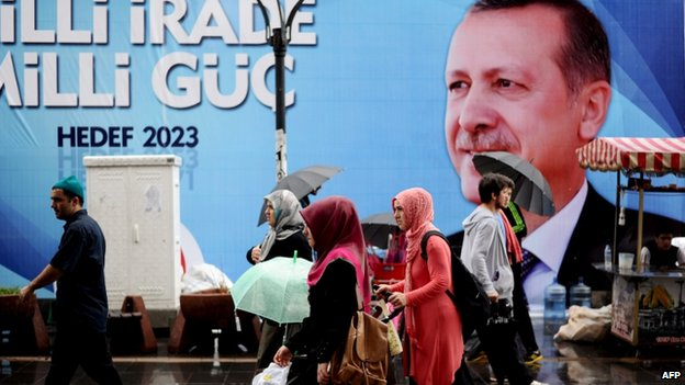 People walk past campaign poster of Turkish Prime Minister Recep Tayyip Erdogan in Istanbul. 9 Aug 2014