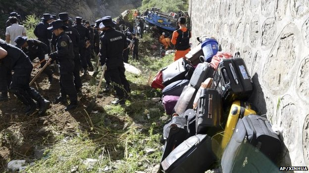 Suitcases of tour bus passengers are piled up as rescuers work near an overturned bus, Aug 9