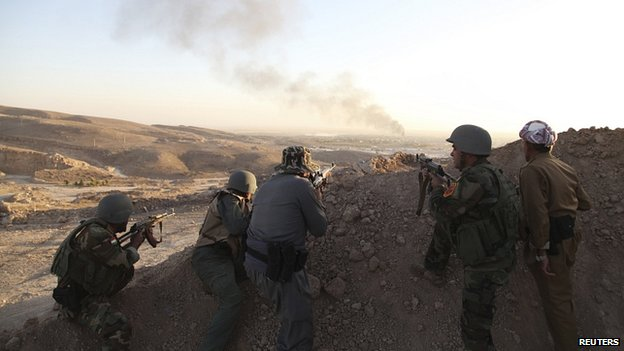 Kurdish forces watch as smoke billows from town of Makhmur during clashes with Islamic State (IS) militants (9 Aug 2014)