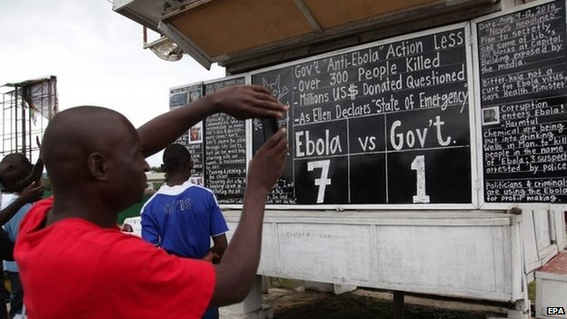 Liberians read the Daily Talk chalk board on the Ebola outbreak situation in Monrovia, 9 August 2014