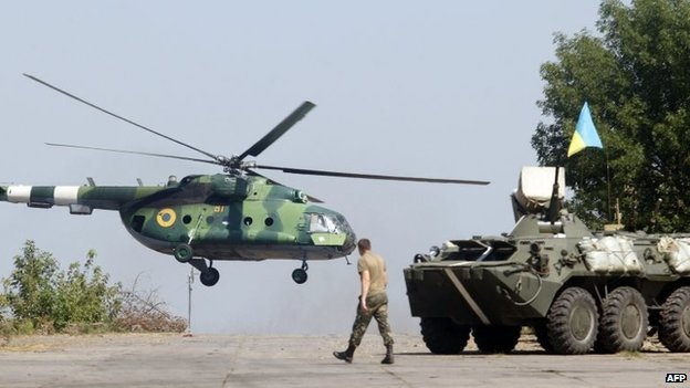 A serviceman walks near an APC while a helicopter flies on the position of the Ukrainian troops in Donetsk region on August 9