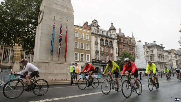 Cyclists ride past the Cenotaph in central London