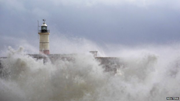 Waves crash against a lighthouse in Newhaven, East Sussex
