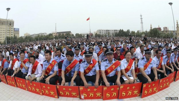 "Police wearing sashes hold placards during a ceremony to award those who the authorities say participated in ""the crackdown of violence and terrorists activities"" in Hotan, Xinjiang on 3 August 2014"