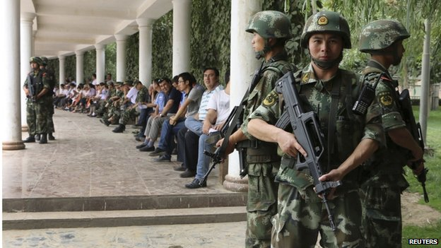 "Paramilitary policemen stand guard during a ceremony to award those who the authorities say participated in ""the crackdown of violence and terrorists activities"" in Hotan, Xinjiang 3 August 2014"
