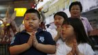 Children pray during the Hungry Ghost festival in Kuala Lumpur on 3 August, 2014