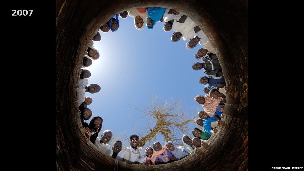 People pictured looking down a well being dug in Khamsa Dagiag camp in Darfur, Sudan - 2007