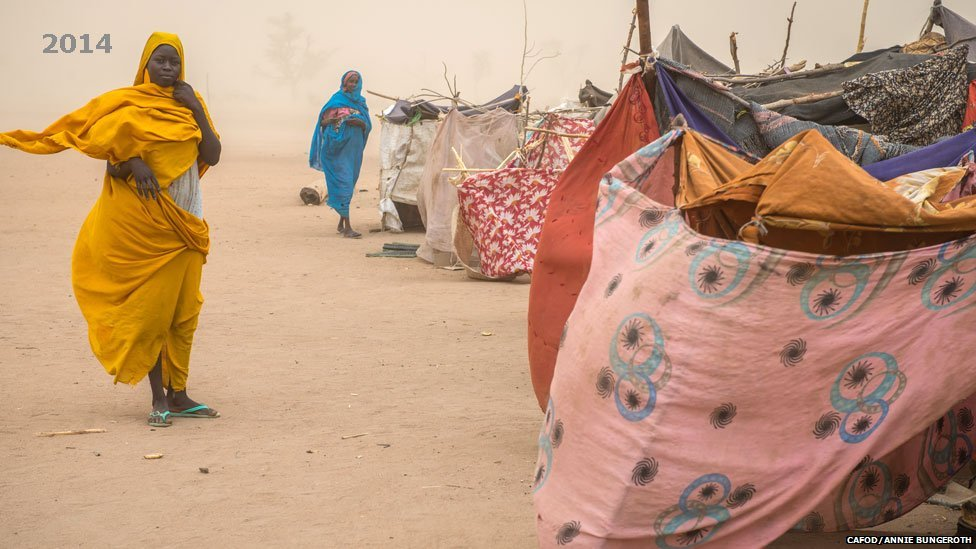 Women pictured during a dust storm at a settlement for those who have newly arrived at Hamadia campin Darfur, Sudan - 2014