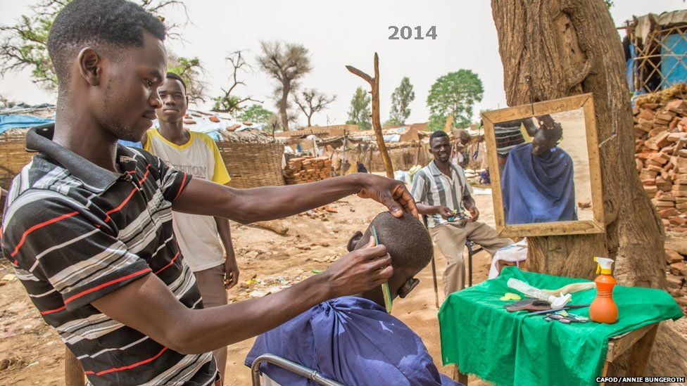 A man cutting hair at Khamsa Dagiag camp in Darfur, Sudan - 2014