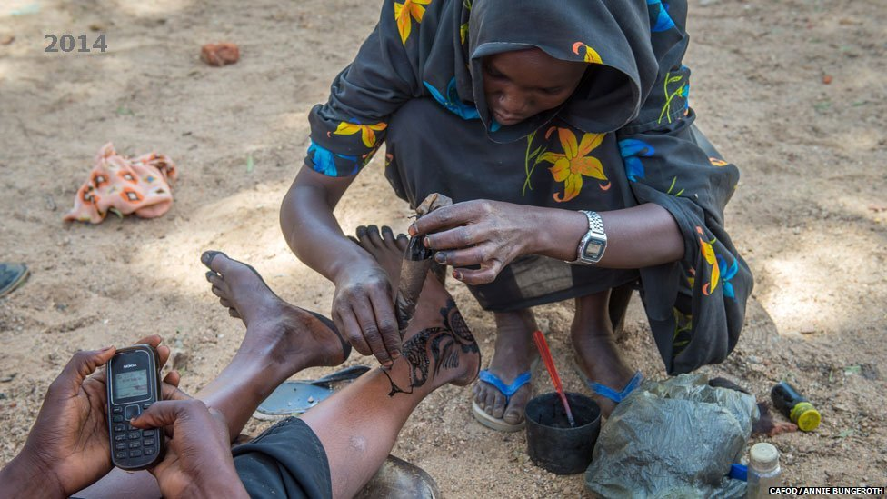 A woman applies a henna dye pattern to another's legs in Hassa Hissa camp in Darfur, Sudan - 2014
