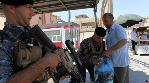 Security forces check man's bags in eastern Iraq - 11 August