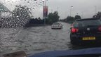 A look from the passenger seat inside a car, view of cars in front wading through a rippling pool of rain water, covering the entire road and coming up to the wheels on the vehicle.