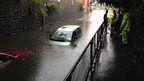 Two cars, one green and one red submerged in rain water in a sloping road underneath a bridge. The rain water comes up to the windows on the car and people gather on the side path looking on.