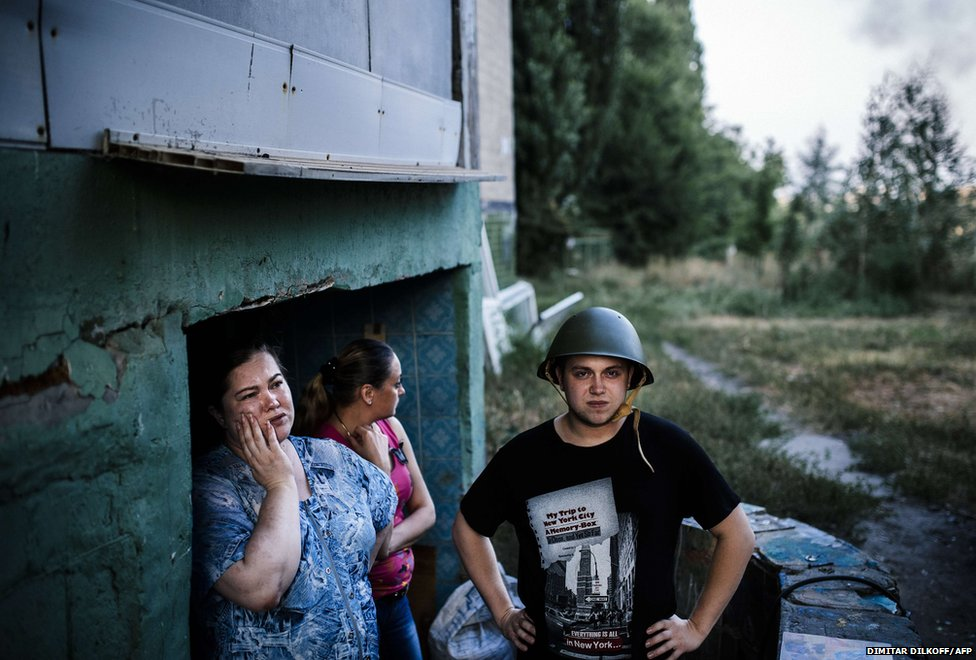 People stand at the entrance of a makeshift bomb shelter in Donetsk,