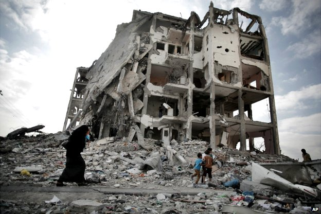 A Palestinian woman walks next to one a destroyed residential tower block in Beit Lahiya, northern Gaza Strip - 11 August 2014