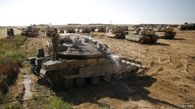 An Israeli soldier washes a tank at a staging area near the border with the Gaza Strip - 10 August 2014