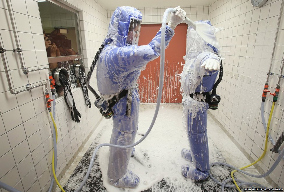 A nurse and a doctor for tropical medicine wearing isolation suits demonstrate the decontamination procedure as part of Ebola treatment capability at Station 59 in Berlin, Germany
