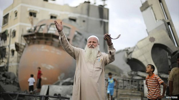 A Palestinian man walks past the remains of the mosque in Khan Younis that was destroyed by an Israeli air strike - 11 August 2014