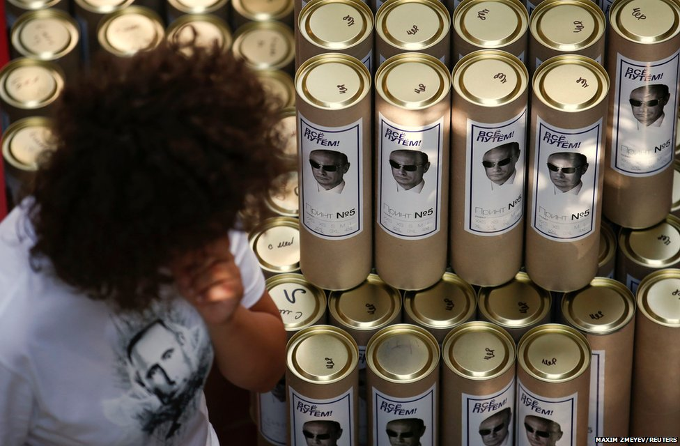 A shop assistant walks past cases containing T-shirts which are printed with images of Russia's President Vladimir Putin, for sale at GUM department store in central Moscow