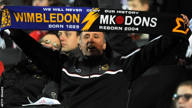 A fan holds an AFC Wimbledon and MK Dons scarf