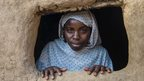 Amina looking out of the window of her house in Khamsa Dagiag camp in Darfur, Sudan - 2014