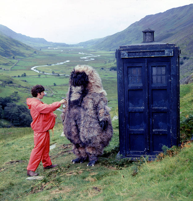 Reg Whitehead as the Yeti standing beside the Tardis with member of the production staff on location in Snowdonia