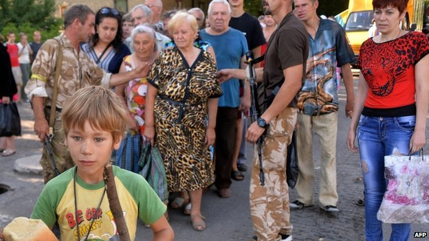 A young boy holds a loaf of bread as residents of the eastern Ukrainian city of Lysychansk queue to receive bread distributed as part of humanitarian aid (27 July 2014)
