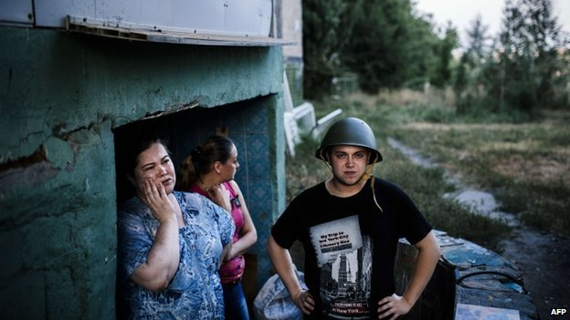 People stand at the entrance of a makeshift bomb shelter in Donetsk, on 10 August 2014.