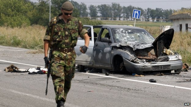 A Ukrainian soldier walks past a damaged car which was used by pro-Russian militants who tried to break through the checkpoint of Ukrainian forces, near the eastern Ukrainian city of Donetsk on 11 August 2014.