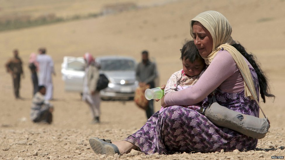 A displaced woman and child from the minority Yazidi sect, fleeing violence from forces loyal to the Islamic State in Sinjar town, rest as they make their way towards the Syrian border, on the outskirts of Sinjar mountain, near the Syrian border town of Elierbeh of Al-Hasakah Governorate on 10 August 2014.