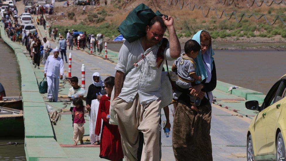 Displaced Iraqis from the Yazidi community cross the Iraqi-Syrian border along the Fishkhabur bridge over the Tigris River at the Fishkhabur crossing, in northern Iraq, on 11 August 2014.