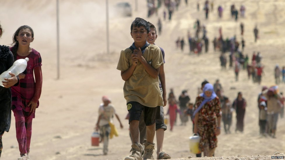 Children from the minority Yazidi sect, fleeing violence from forces loyal to the Islamic State in Sinjar town, make their way towards the Syrian border, on the outskirts of Sinjar mountain, near the Syrian border town of Elierbeh of Al-Hasakah Governorate August 10, 2014