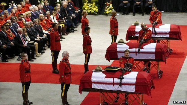 Royal Canadian Mounted Police officers collect possessions from the caskets of three fellow officers who were killed last week during a regimental funeral in Moncton, New Brunswick, 10 June 2014