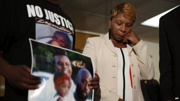Lesley McSpadden, the mother of 18-year-old Michael Brown, wipes away tears as Brown's father, Michael Brown Sr., holds up a family picture of himself, his son, top left, and a young child during a news conference 11 August  2014