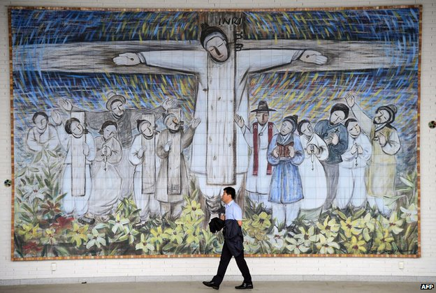 "A man passing in front of a huge wall painting for Korea""s Catholic martyrs at Solmoe Shrine in Dangjin (7 August 2014)"