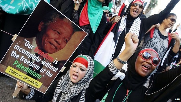 Women gestures while one holds a picture of late former South African president Nelson Mandela as they march through the streets of Durban following Friday prayer on 25 July  2014